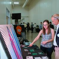 An engineering student explains her LED signage project to a guest at the Engineering Design Project Preview